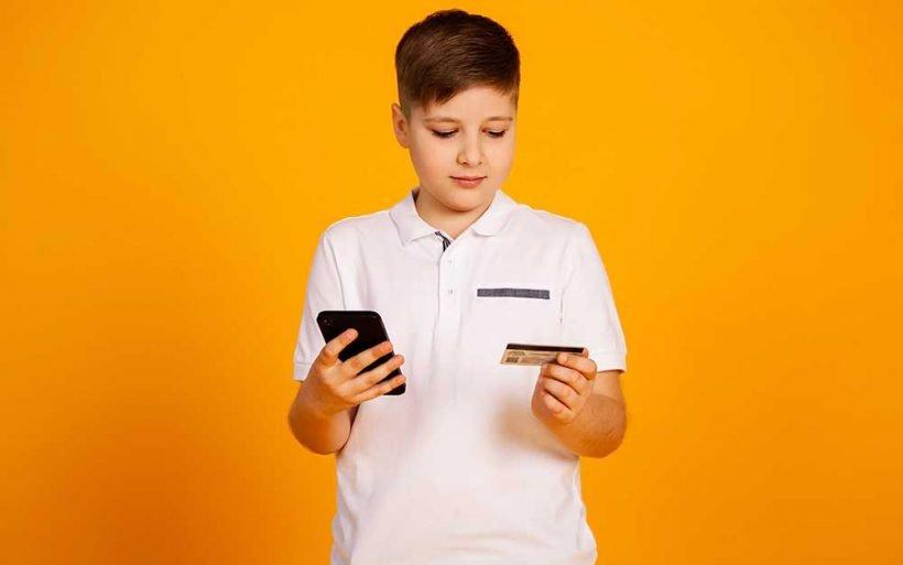 Chłopiec wybiera metodę płatności na telefonie